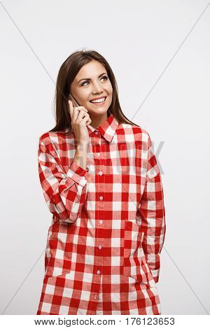 Charming young woman in trendy long check shirt making phonecalls, looking away with smile