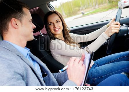 Driving instructor and woman student in examination car.