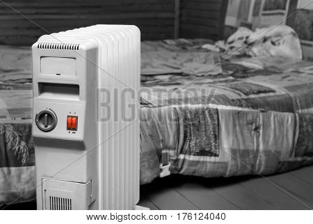Electric heater powered on next to a bed selective color shot with focus in the foreground