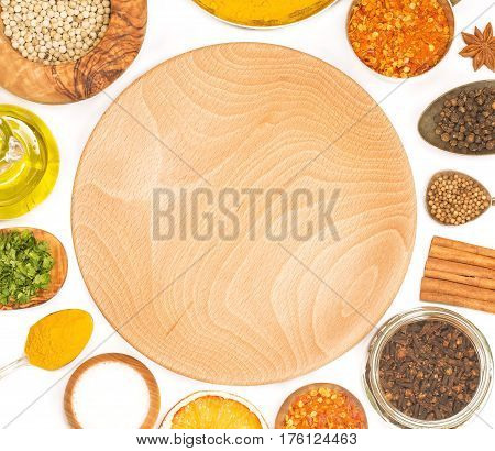 Various spices with a wooden plate isolated