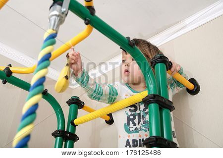 Child climbing to banana on gymnastic bar.Children workout. Child health care and physical training concept. Happy and healthy childhood. Kid playing jungle monkey