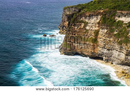 The cliffs and the ocean near the Uluwatu Temple on Bali Indonesia. waves crashing against the cliff