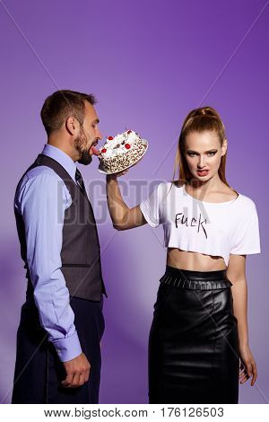 Handsome man in suit and young beautiful brutal girl prepare fight with cake over purple background. Copy space.