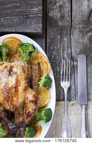 Roasted chicken with garnish on wooden background