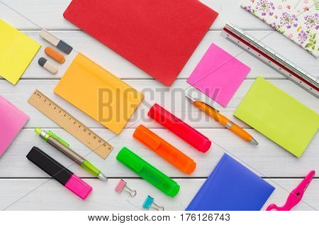 Flat lay of office and school stationery supplies - set of colorful markers, sticky notes, notepads, pens, rulers and erasers on white wooden table background, top view, nobody, objects