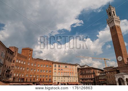 Tower of Mangia, piazza del Campo, Sienna, Italy, with nearby buildings and dramatic sky