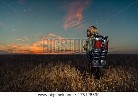 Boy with a backpack at night