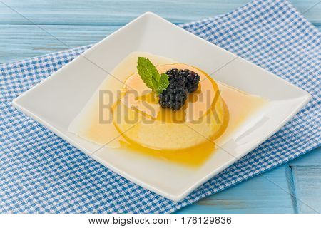 Passion fruit flan with blackberries and mint on white plate.
