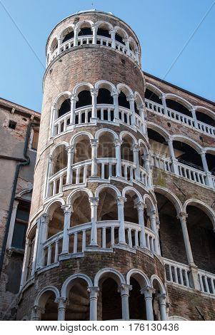 Ancient cylindrical staircase stone tower, Venice, Italy with white arches and pillars