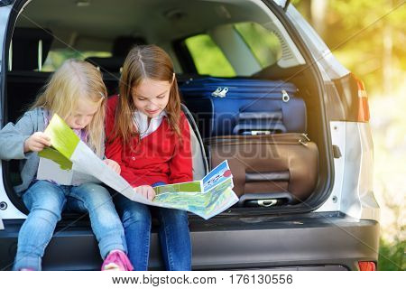 Two Adorable Little Girls Ready To Go On Vacations With Their Parents. Kids Sitting In A Car Examini