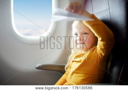 Adorable Little Girl Traveling By An Airplane. Child Sitting By Aircraft Window Playing With Paper P