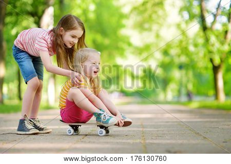 Two Pretty Little Girls Learning To Skateboard On Beautiful Summer Day In A Park