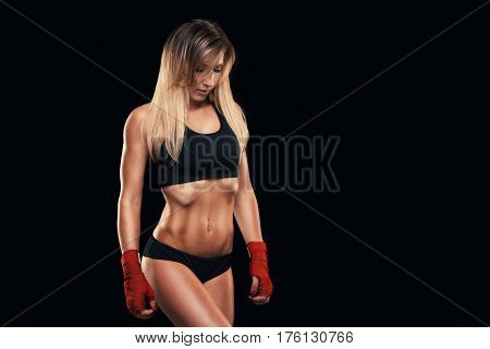 athletic girl posing in red bandages, isolated on the dark background. boxing fighter kickbox