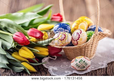 Easter. Hand made painted easter eggs in basket and spring tulips.