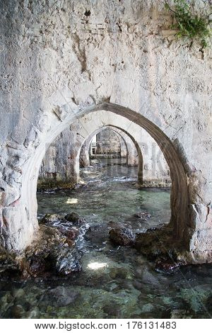 Arches made of stone inside shipyard of Alanay medieval castle built in XIII century by Alaeddin Keykubat with turquoise water