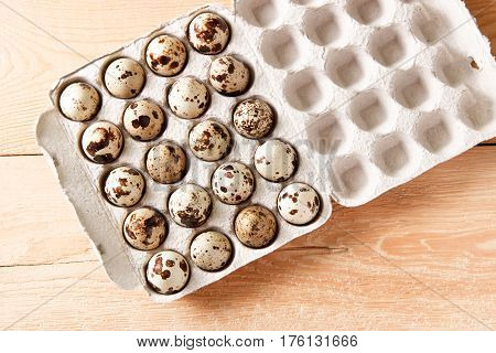 Quail eggs in a container on a wooden background