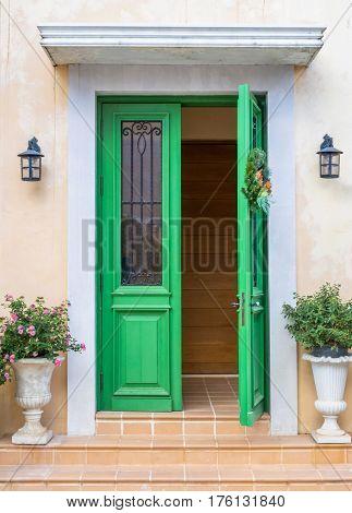 Green door European style.The door opens with a flowerpot on the front.