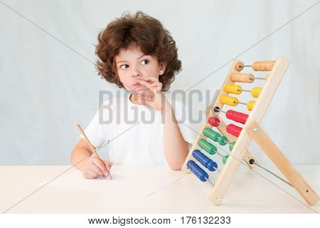 Cute curly-haired boy in a white shirt thinking of the solution of the task. Gray background.