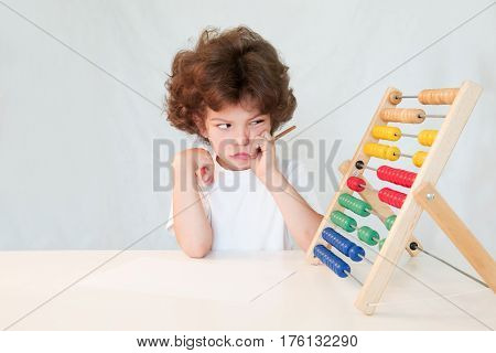 Weeping cute boy squinting eyes looking at the scores. Sits by the table. Gray background.