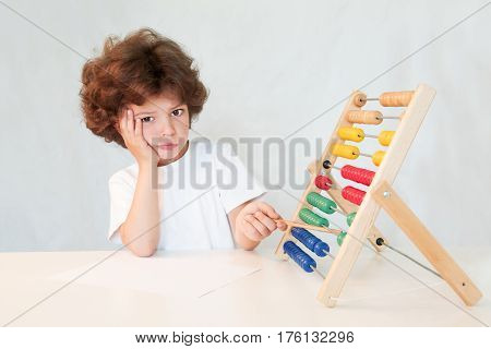 Weeping cute boy with a pencil indicating scores. He looks into the camera. Sits by the table. Gray background.