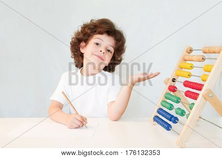 Cute curly-haired boy with a pencil in his hand indicating scores. Close-up. Gray background.