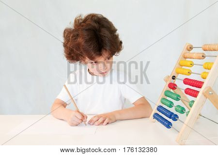 Cute curly-haired boy writes in pencil on the paper and looks at scores. Close-up. Gray background.