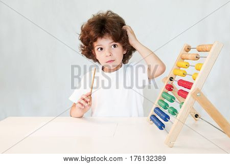 Cute curly-haired boy with a pencil in his hand thoughtfully scratching his head and looking at the camera. Close-up. Gray background.