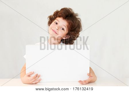 Happy cute boy with interest looks at the camera. Holding in hands a white box. Gray background.