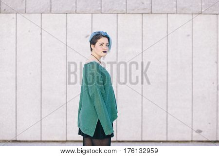 Teen androgynous woman with blue dyed hair isolated on the street wearing a blue sweater. poster