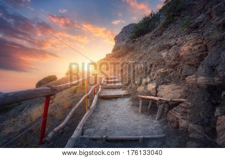 Stone Stairs With Wooden Railing In The Mountains At Sunset