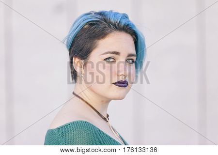 androgynous young woman wearing a piercing with blue dyed hair isolated on the street