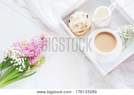 Morning breakfast in spring with a cup of black coffee with milk and pastries in the pastel colors a bouquet of fresh pink hyacinth on a white background. Top view.