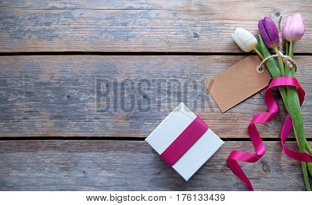 Flowers with blank gift label over a wooden background