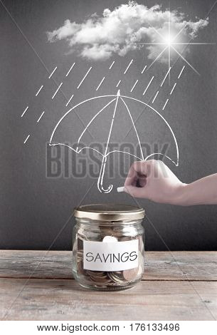 Umbrella being sketched on a chalkboard protecting a jar of savings