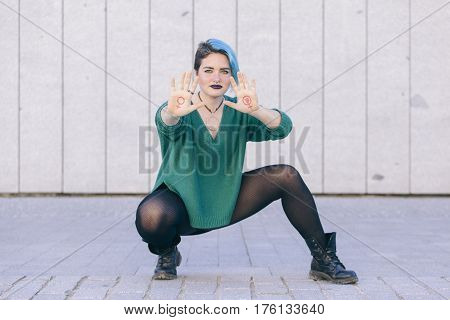 androgynous young strong woman fighting for feminism equality isolated on the street