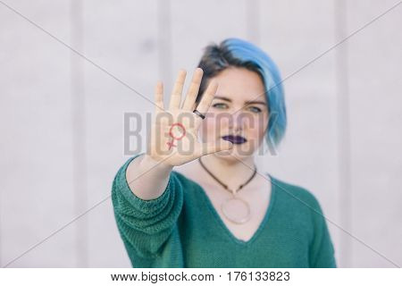 pink symbol of feminism written on a woman hand isolated on the street