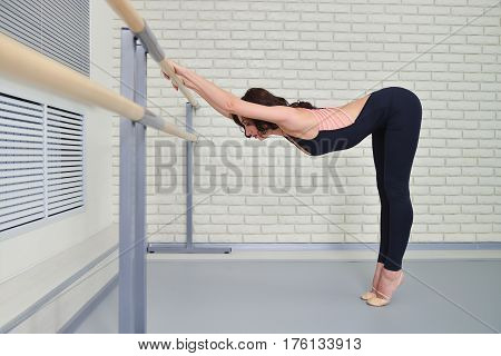 Ballerina stretches herself near barre in the classroom, beautiful women stretching.
