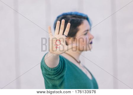 pink symbol of woman feminism isolated on a hand of a teenager