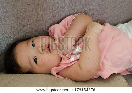 Handsome and cute asian baby playing on the grey sofa.