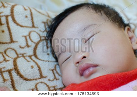 Handsome and cute asian boy sleepig on the bed.