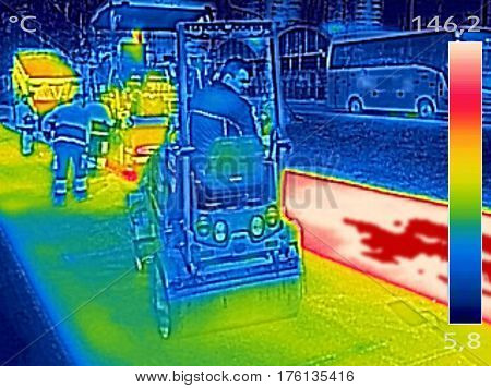 Infrared thermovision image showing Workers on Asphalting paver machine during Road street repairing works