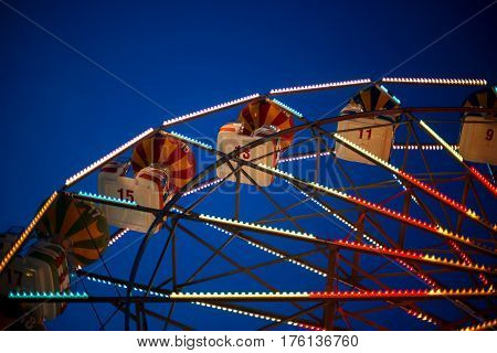 Part of the Ferris wheel at night with bright lamps