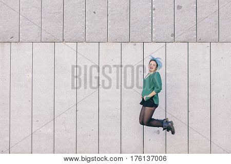 teen androgynous woman jumping with blue dyed hair isolated on the street wearing a blue sweater.