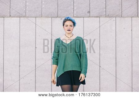 Teen androgynous confident woman with blue dyed hair isolated on the street wearing a blue sweater.