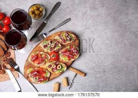 Tasty bruschetta served with wine on gray background