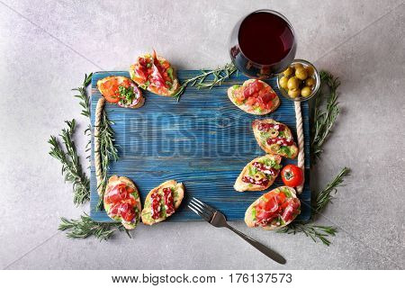 Wooden board with tasty bruschetta and  wine on light background