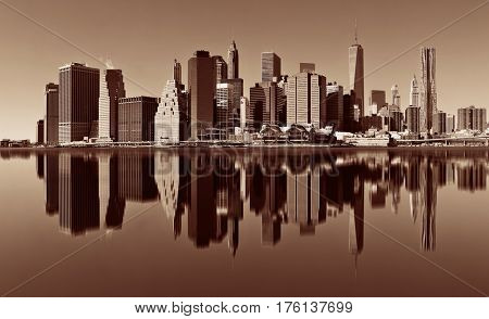Manhattan financial district with skyscrapers over East River with reflection.