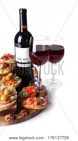 Tasty bruschetta served with wine on white background
