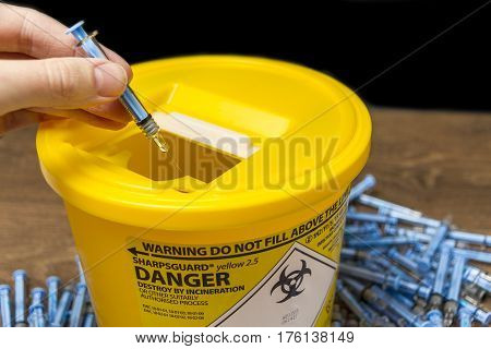 Used Needles and Syringes being put ito a sharps bin