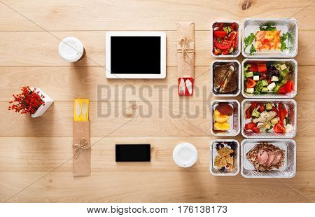 Online healthy restaurant food order, diet plan. Fresh daily meals delivery. Fitness nutrition, vegetable, meat and fruits in foil boxes, coffee and tablet. Top view, flat lay on wood with copy space
